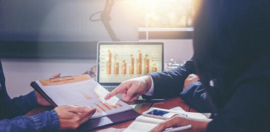 Três pessoas reunidas apresentando gráficos de fundos de investimentos