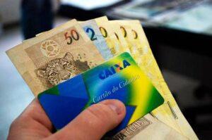 Mão segurando cartão cidadão e notas de dinheiro