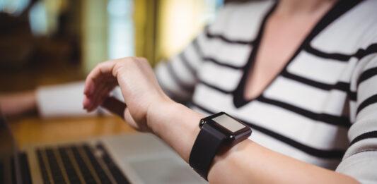 Notebook aberto com o braço de uma mulher com relógio