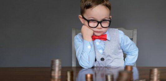 criança encara pilhas de moedas