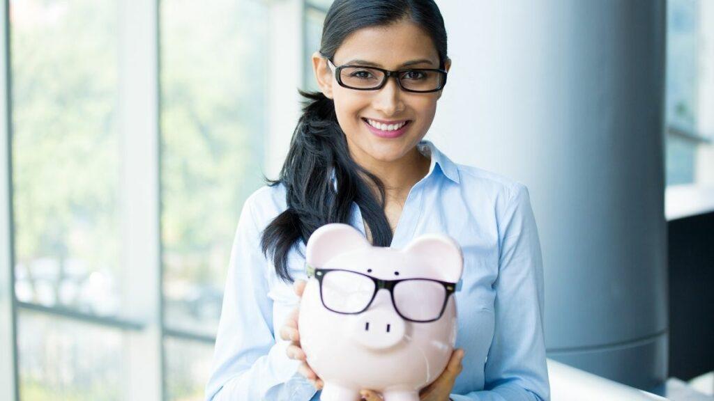 mulher segura cofre em formato de porco