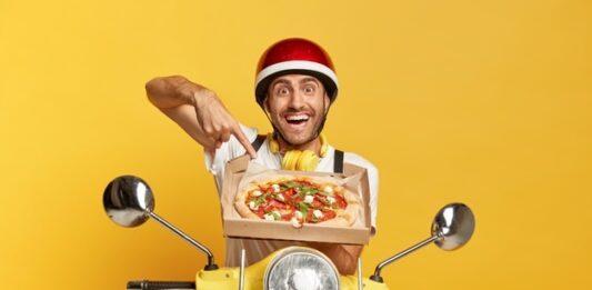 Entregador de pizza delivery sorrindo em uma moto amarela