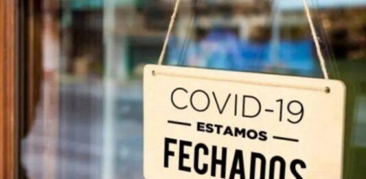 placa de loja fechada com o aviso: covid-19 - estamos fechados