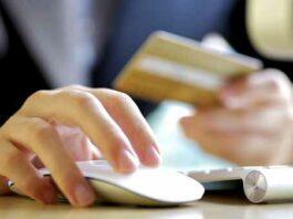 pessoa mexendo no computador segurando cartão de crédito