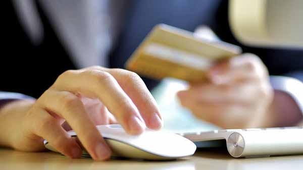 pessoa mexendo no mouse do computador segurando cartão de crédito