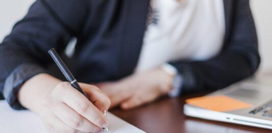Pessoa escrevendo em um papel
