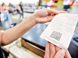 pessoas segurando uma nota fiscal após a compra