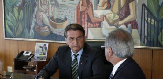 Presidente Jair Bolsonaro e Ministro da Saúde Paulo Guedes conversando em uma mesa