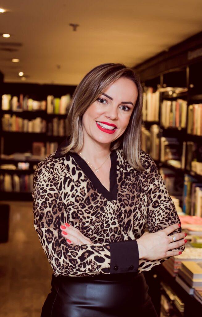 Foto da especialista Odineia Silva, de braços cruzados e sorrindo, para falar sobre reserva financeira