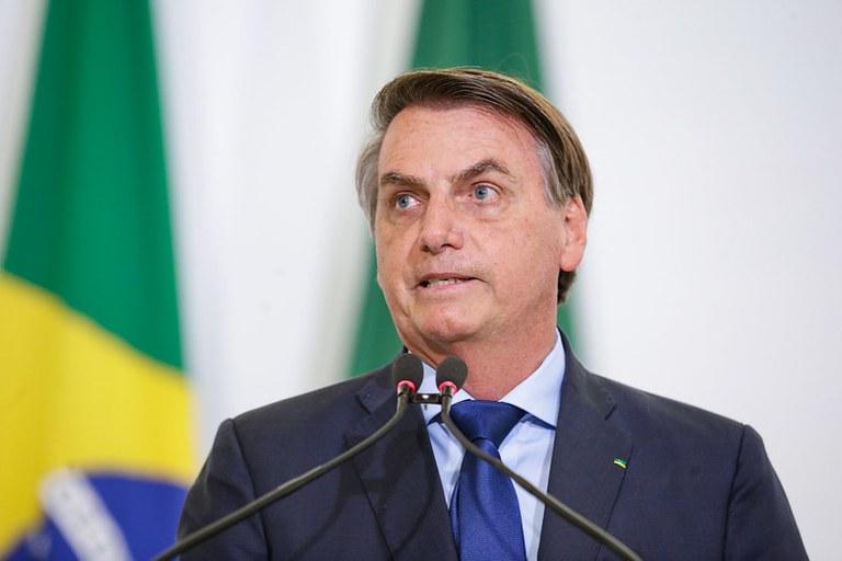 auxílio emergencial 2021: presidente Jair Bolsonaro em frente ao microfone para discursar