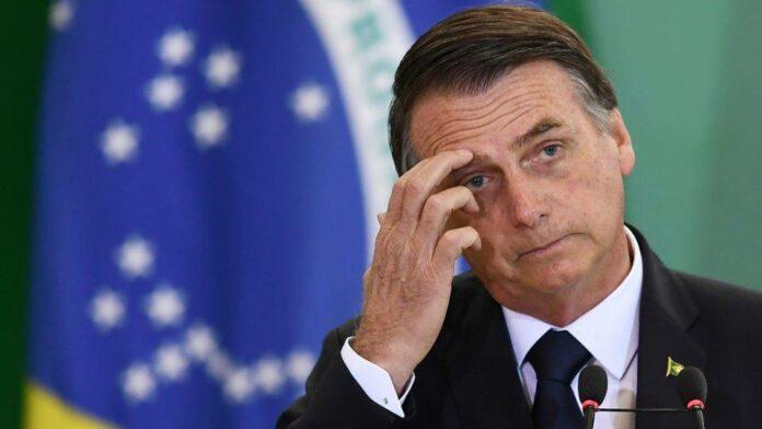 Bolsonaro com a mão na cabeça e atrás a bandeira do Brasil desfocada