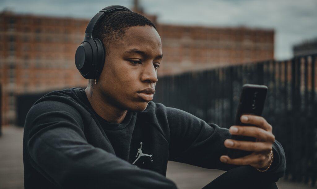 Homem negro sentado e mexendo no celular com fone no ouvido para ver aplicativos para cashback