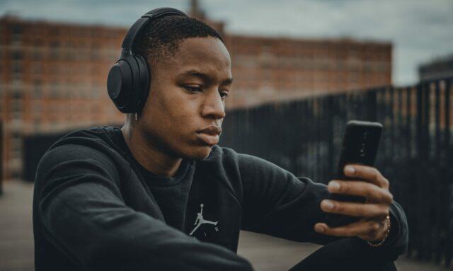 Garoto com fone de ouvindo usando celular para finanças