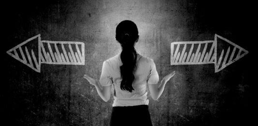 Mulher escolhendo qual direção escolher: esquerda ou direta, representada por duas setas