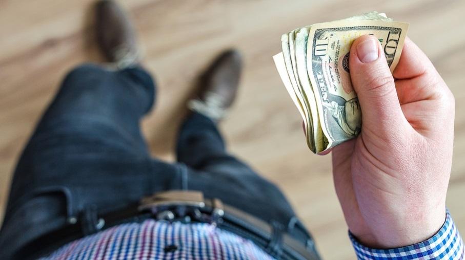homem visto de cima segurando dólar nas mãos