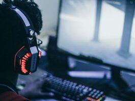 Homem com fone de ouvido jogando videogame no computador