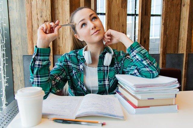 Mulher sentada e pensativa com cadernos e livros