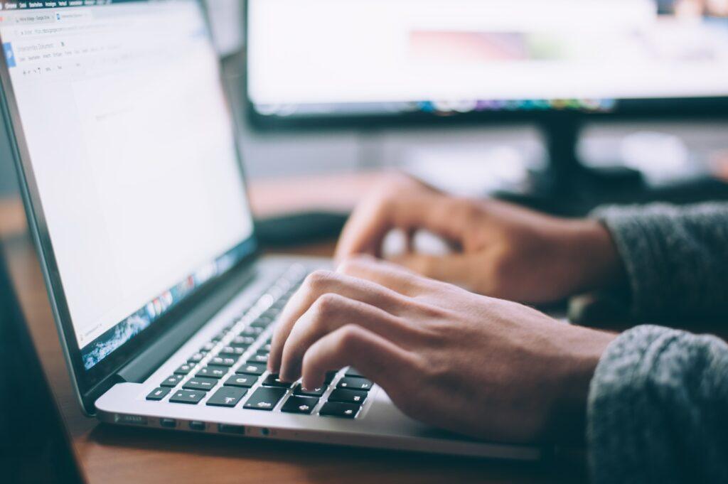 Pessoa escrevendo no notebook para ilustrar o texto sobre curso de inglês online