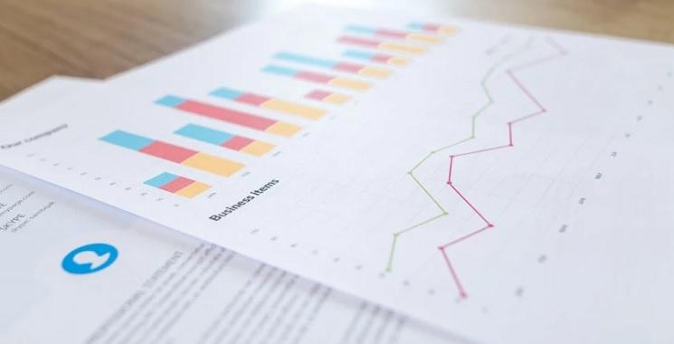 Papéis com gráficos de investimentos em uma mesa de madeira