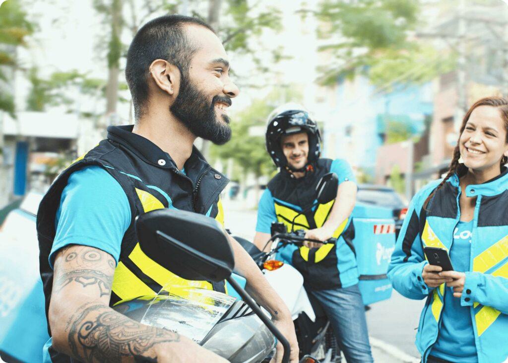 Dois homem e uma mulher. Todos sorrindo e são funcionários da empresa. Estão de coletes azul e amarelo. Foto para ilustrar o texto sobre Loggi para empresas