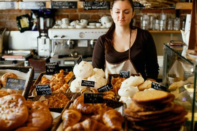 Imagem que contém uma mulher branca olhando para os produtos em uma padaria para ilustrar o texto sobre dispensa de alvará para MEI