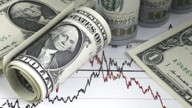 Notas de dólar enroladas em um papel com gráficos