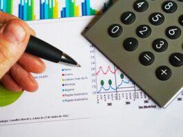 Mão com caneta escrevendo em um papel com gráficos com calculadora