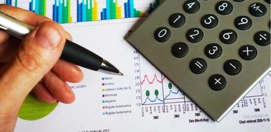 Mão com caneta escrevendo em um papel com gráficos e calculadora
