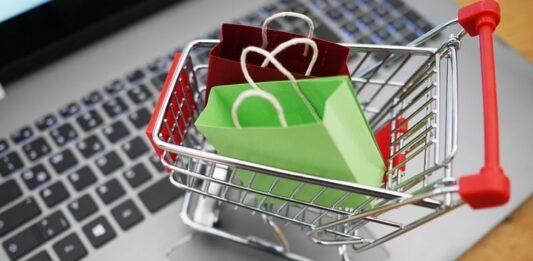 Carrinho de compras em miniatura carregando 2 pacotinhos de compra em cima de um notebook