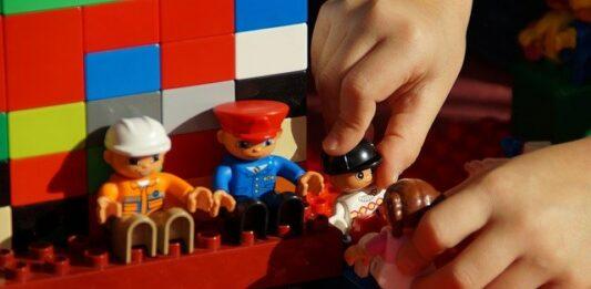 Criança brincando com legos e playmobil
