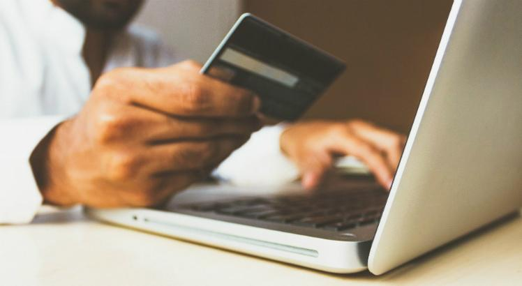Homem fazendo compras na Black Friday usando notebook e cartão de crédito