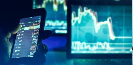 Pessoa acessando investimentos no celular e computador, que exibem gráficos
