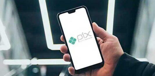 Homem segurando celular com imagem de PIX na tela