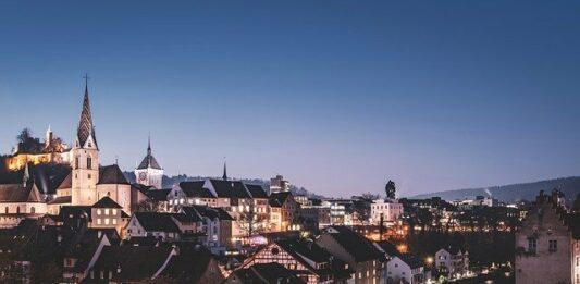 Cidade da Suíça com casas iluminadas ao anoitecer