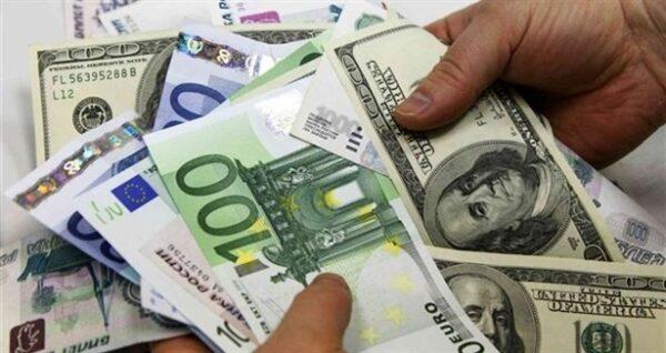Mão segurando notas de euro e dólar