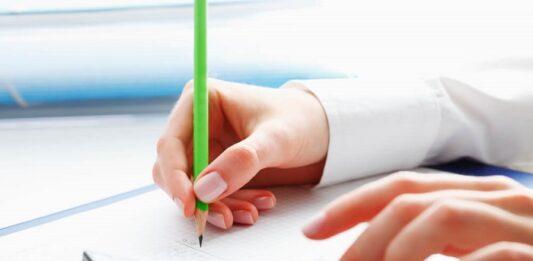 Pessoa escrevendo com lápis verde e usando calculadora