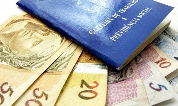 carteira de trabalho com notas de cinquenta, vinte, dez e cinco reais