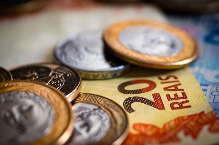 moedas em cima de uma nota de vinte reais