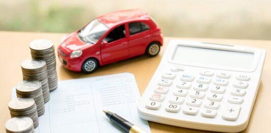 Calculadora, papeis com anotação, caneta, moedas empilhadas e um carro vermelho em miniatura