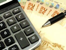 Calculadora sobre a mesa com notas de dinheiro