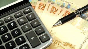 calculadora, caneta preta e cinco notas de cinquenta reais