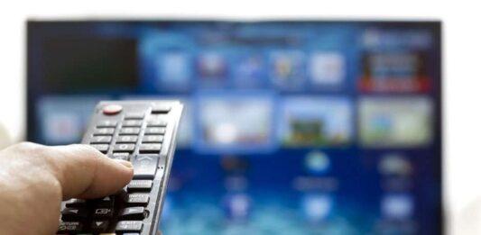 Pessoa usando controle remoto e uma tv grande ao fundo