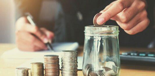 Pessoa depositando moeda em um pote transparente com moedas e 4 fileiras de moedas em um pote