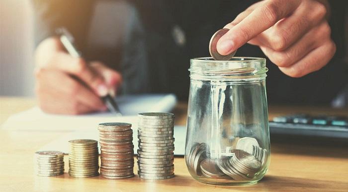 Pessoa depositando moeda em um pote transparente com moedas e 4 fileiras de moedas ao lado
