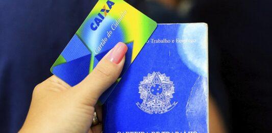 Mão feminina segurando carteira de trabalho e cartão cidadão