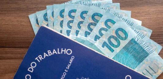 Carteira de trabalho com notas de 100 reais