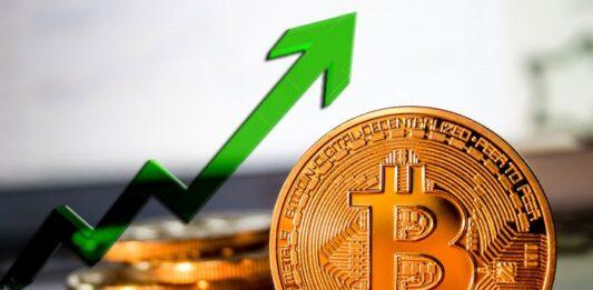 Gráfico em seta verde ao lado de uma criptomoeda do Bitcoin