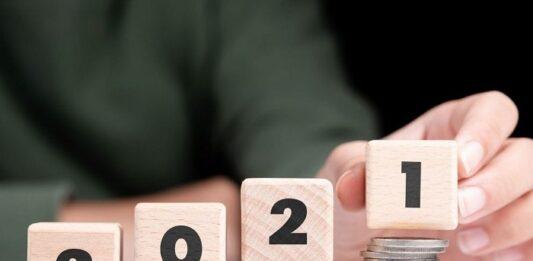 Pessoa empilhando quatro pequenos blocos de madeira com os números de 2021 em cima de moedas enfileiradas
