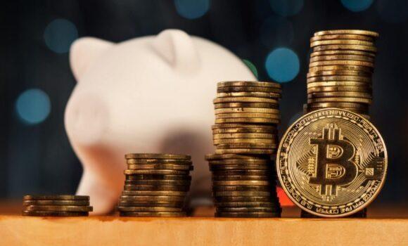 Cofrinho de porco com várias moedas de Bitcoin enfileiradas