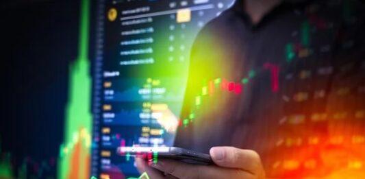 Montagem de uma pessoa acessando celular com efeitos de vários gráficos de investimentos coloridos